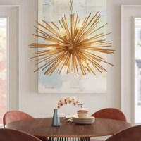 Greet guests with a warm and welcoming glow in the entryway or dress up your dining room for an upcoming dinner party with this eye-catching chandelier. Sure to make a statement in any setting, it is a metal frame takes on a sputnik-inspired silhouette with bursting rays all finished in gold for a glint of glamour. Twelve lights are distributed throughout, each exposed to create an even gleam. Installation is required for this hardwired fixture.