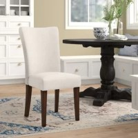 To fully enjoy a homecooked meal with friends, family, or by yourself, a dining chair that promotes proper posture while lending an eye-catching focal point to your dining ensemble is a must-have. Take this one for example: Crafted from solid wood, it features foam-filled linen upholstery awash in a solid neutral finish for a look that complements nearly any color palette in your traditional aesthetic. Arrives in a set of two.