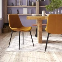 This Neilson Upholstered Dining Chair with refined modern style and quality craftsmanship. Slightly curved seat is upholstered with caramel brown faux leather. Black iron legs are steady and durable.