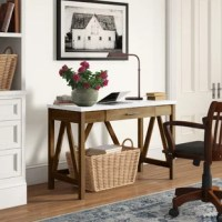 Rustic style meets modern flair in this curated writing desk. Crafted of manufactured wood with laminate veneers, the desktop strikes a clean-lined rectangular silhouette – perfect for propping up your laptop and accessories. Its rustic woodgrain trestle base includes one pull-out drawer for stowing files and office supplies.