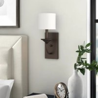Whether illuminating the entryway or brightening up your bedroom, this wall sconce offers both style and light. Crafted from metal, its frame pairs a rectangular backplate and curved arm finished in a metallic tone for a look that works well in classic and contemporary settings alike. Its single light is highlighted by an off white-hued fabric shade to evenly distribute the glow. Rated for dry areas only, we do not recommend using this light in bathrooms with steamy showers.