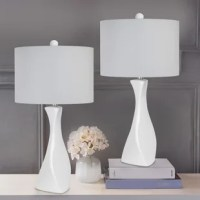 This beautiful ceramic table lamp showcases a squared base that twists up into a curvaceous yet angular body featuring a gorgeous finish. Topped by a linen drum shade and a ceramic finial, this table lamp will add a fun, modern aesthetic to any space. Whether resting on your nightstands, set on side tables in your den, or tucked into your favorite reading nook, these lamps are the stylish solution to your lighting needs.