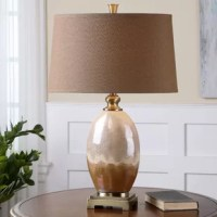 Ceramic base finished in an iridescent ivory and brown glaze accented with brushed gold details. The tapered empire hardback shade is a brown linen fabric with natural slubbing. Due to the nature of fired glazes on ceramic lamps, finishes will vary slightly.
