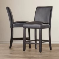 These pub style side chairs offer luxurious seating as well as stylish design. Complete with a black wood finish, these chairs feature a padded foam-filled interior with tightly wrapped faux leather upholstery. A thick welt trim lines these chairs for a stylish finishing touch.