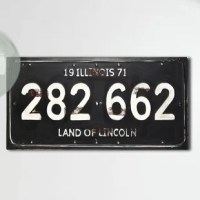 This simple wall sign is a great way to celebrate your home state or the perfect reminder of a wonderful family trip. This black and white plaque features the word Illinois and the phrase Land of Lincoln above and below license plate - style style numbers. It makes a wonderful gift for anyone who loves Illinois and looks great hanging up in the shop kitchen living room or bedroom.