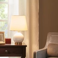 The Linden Table Lamp's shapely marble sphere is a glamorous statement piece on any bedside tables and desks.  Finished with antique gold accents, our table lamp is paired with a warm white shade.