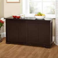 With a clean-lined look suited for transitional spaces, this accent cabinet is more than just a place to put your things – it's a style statement! Crafted from manufactured wood, it stands atop bracket feet and features inset paneling for a hint of classic charm, while an espresso finish lets it blend in with a variety of color schemes. Sliding doors conceal two shelves on which you can place serve ware, spare linens, books, and more.