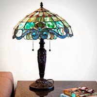 This Tiffany-style table lamp uses a combination of ripped and striated glass in its shade, while also showcasing 201 pieces of handcrafted glass, and 30 pieces of glowing cabochons. The top of the shade showcases a diamond pattern with amber and green hues that lead to blue hues around the bottom of the shade, and accent the scalloped edges and scrolling details. This lamp accommodates two incandescent 60 W bulbs below the shade (bulbs not included).