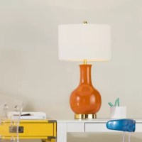 Lightweight, portable, and mindful of space, table lamps keep your home looking on the bright side with just-right task and accent lighting. Take this one, for example, the perfect pick for any mid-century-inspired space, it features a circular base awash in gold and round frame boasting a solid color. Up top, the included white empire shade helps increase ambiance and accommodates one 13 W E26 light bulb (included).