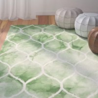 Transform a cozy seating ensemble into a bohemian-inspired living room look with this eye-catching handmade rug, featuring a dip-dyed design and a trellis motif in green and ivory.