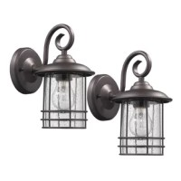 Tastefully blending traditional style with factory flair, this is an updated classic. Featuring weather- and dust-resistant design, this fixture features a round backplate, a curlicue arm, and a single 100 W type A bulb (not included) ensconced within a clear seeded glass shade. An open cylindrical wire cage completes the look with a dash of industrial influence. Since this luminary comes in a set of two, it's perfect for flanking a front door.
