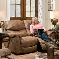 This reclining loveseat is upholstered in 100% polyester and accented with nail trim. With the luggage stitching, rounded wings, and arms, this piece is sure to make a statement in your home.