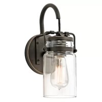 Showcasing the perfect modern vintage look, this 1-light wall sconce brightens up your hallway, entryway, bathroom and more. Inspired by mason jars, its cylindrical clear glass shade gives the design familiar appeal. But instead of a lid, this shade features a metal top that's held by an arched arm, which connects to a rounded backplate – all finished in a neutral hue. This sconce requires a 60W bulb (not included) – we recommend adding an Edison bulb!