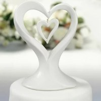 This stylish Double Heart Cake Topper is perfect for the more modern couple. Made of porcelain and a small porcelain heart dangles inside a larger heart, two hearts joined together as one.