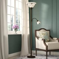 Illuminate your space in an elegant, transitional style with this Torchiere floor lamp. Crafted of iron in a curated finish, this lamp features a slender pole body and a round pedestal base accented by decorative carvings. Capped with a glass dome shade, an adjustable gooseneck arm off the side of the post lets you direct light where it's needed most from an E12 bulb, while a matching inverted dome shade up top casts ambient light throughout your space from an E26 base bulb.