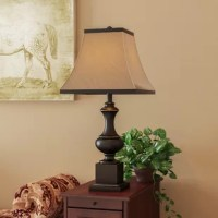Set your space all aglow while also upping the traditional charm with this timeless table lamp. Standing at 27.5 inches tall, its ornate base is crafted of metal with classic turned details finished in dark bronze. Its single light is highlighted by an elegant square empire shade, woven of fabric and featuring a beige hue with a dark border. Simply set it atop a polished wood end table to put the finishing touch on your living room seating ensemble, then play up its stately style with handsome...