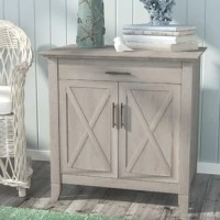 Not just an accent piece suited for modern farmhouse ensembles, this cabinet features a pull-out keyboard tray that instantly transforms it into a small-scale work station. Crafted from manufactured wood, it stands atop post legs and features doors fronted by x-shaped accents to evoke the look of a barn door. While the doors conceal plenty of storage space for your bits and bobs, the keyboard tray up top features plenty of room for a laptop or keyboard and mouse.