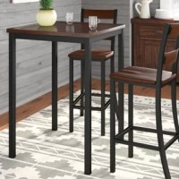 Pub tables are perfect for bar areas, or dining areas short on square footage. Take this table, for example, standing on four straight legs, in a neutral black hue that can blend in with most color palettes, you can pair it with your choice of pub chairs or bar stools. Perfect for traditional or rustic aesthetics, this square table is constructed from metal with wood veneers, and measures 42'' H x 30'' L x 30'' W. It accommodates four people comfortably.