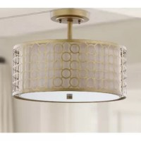 A distinctive marriage of a cream fabric shade with geometric-patterned laser cut steel in antique gold finish, this ceiling light showcases the glamorous drum shade-within-a-shade trend. This ceiling light is ideal for a transitional kitchen, bedroom, or hall.