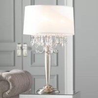 More than just illumination for your abode, table lamps lend artful appeal to your space as they shine. Try adding one to your nightstand to give the master suite a mini makeover, or stage one atop the entryway console to greet guests with a warm glow. Take this one for example: gleaming with glamour, it pairs a brushed silver-finished metal base with cascading crystal accents below its tapered drum shade.