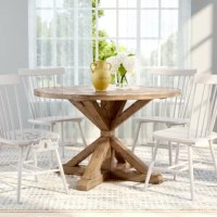 Defined by a cinched pedestal design, open x base, and classic round top, this understated and rustic pine wood, and MDF dining table lends a bit of classic cottage charm and updated, contemporary appeal to your ensemble. Set it on a neutral-toned, woven sea grass rug in the dining room to round out your subtly chic aesthetic, then center it with a blooming faux peony bouquet to tie a garden-chic twist into the group. Pull up a group of button-tufted, charcoal-toned side chairs to gather family...