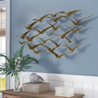 For a breezy, tropical-inspired look in the master suite or living room, simply add this wall decor! Taking on the shape of stylized birds in a flock, it's crafted from metal with a brass gold finish. Measuring 21'' H x 47'' W, it can act as the focal point of the spot over the couch or seamlessly blend into existing wall accents. Holes in the back let you hang it up with ease.