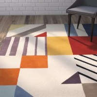 An eye-popping addition to your decor, this hand-tufted wool area rug instantly elevates any casual space. Its geometric details add a pop of pattern to your decor, while its multicolor palette is perfect set against a rich hardwood floor for a contrasting look. Lean into this rug's versatility by adding it to a contemporary living room alongside a mid-century armchair and complementing loveseat for cohesive seating space. Dot nearby walls with metal geometric accents and abstract...