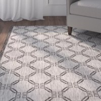 Update any space – indoors and out – with a fresh look by rolling out this area rug! Woven in Turkey from resilient polypropylene fibers, this rug is designed to stand up to both water and fading, so it's great in living rooms as well as on your patio or deck. Plus, thanks to its eye-catching geometric pattern in ivory and charcoal hues, it's perfect for a versatile look. Best of all, this rug is easy to care for: Just vacuum without a beater bar, or even rinse it with a hose!