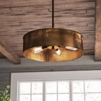 Defined by its exposed bulbs and round drum shade, this metal pendant is sure to spark conversation in your well-appointed home. Its weathered brass finish is perfect set against a crisp white wall for a contrasting look, while its open design brings breezy flair to any space. Play up this piece's factory inspiration by adding it to an industrial entryway alongside an exposed-wood console table and rich leather bench for a cohesive arrangement. Dot nearby walls with gear-inspired decor and...