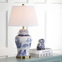 Inspired by antique Chinese pottery depicting mountain and forest scenes, the Shanghai ginger jar lamp is in keeping with fashion's renewed reverence for Asian design. This classic lamp is crafted of ceramic with white linen shade and antique gold accents.