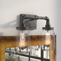 Inspired by factory designs and vintage accents, this distinctive two-light vanity light lends your powder room an industrial edge. The rectangular backplate and pipe-style arms are crafted from steel in a rustic black finish for understated appeal, while a pair of clear glass shades modeled after Mason jars complete the look with a touch of modern farmhouse flair. Though this luminary accommodates any 100 W medium-base A19 incandescent bulbs (not included), we recommend you pair this piece...