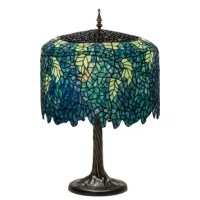 Cascading blossoms in variated hues of blue glass with spring green leaves were favored subjects of the L. C. Tiffany studio. Beautiful Wangaratta stained glass shade with undulating border. Paired with a natural-looking tree trunk base in an antique patina finish.