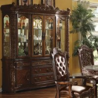 This traditional dining collection features a double pedestal dining table complemented with oversized upholstered chairs all accented by floral carving. Matching hutch and buffet reflects all carefully selected design features as the dining collection.