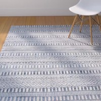 Expertly playing with texture, pattern, and fabrics, this charismatic Firenze Hand-Woven Wool Ivory/Blue Area Rug instantly elevates any floor in your well-appointed home. Handwoven in India from a wool and cotton denim blend, this dapper design showcases tribal-inspired design in muted hues of ivory white and indigo blue. Establish a retro chic aesthetic in your living room by rolling this area rug to define the space, then arrange a track armed leather sofa and a chrome-framed Barcelona chair...