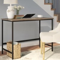 Simplistic as it may seem, this understated writing desk is a must-have for traditional spaces and farmhouses alike. Crafted of black-finished metal, its clean-lined frame is accented by a laminated MDF top for a look of classic rustic charm. Add on a collection of framed family photos and a few lush potted plants for an eye-catching living room display behind a tufted sofa, perfect for tying the whole ensemble together. But wait - pull up an upholstered rolling chair and suddenly you have a...