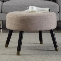 Lend a touch of midcentury modern appeal to your space with this tastefully retro ottoman. Made from solid rubberwood, this dapper design showcases a simple circular silhouette with a upholstered cushioned seat and four flared, tapered round legs. Establish a sparse, Scandinavian-inspired aesthetic in your open concept living room by rolling out a micro-herringbone area rug to define the space, then place asymmetrical end tables between a low-profile track arm sofa and a walnut-framed armchair...