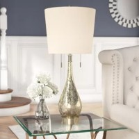 """A glam contemporary take on midcentury style, this fabulous 40"""" table lamp lends your space chic style with a twist. Set on a sleek, cylindrical, brushed steel base, this dapper design showcases a teardrop-shaped mercury glass body contrasted by a hardback drum shade. Establish a refined, luxurious aesthetic in your open concept living room by rolling out a soft gray damask area rug to define the space, then set a mirror plated console table by a brightly-lit window dressed in fringed satin..."""