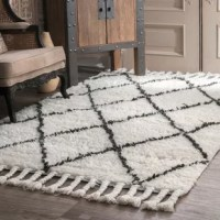 Lay a bohemian foundation for your stylish space with this off-white and dark gray area rug, featuring a chic diamond motif and 5'' tassel trim. Made in India, this rug is hand-knotted from wool in a medium 0.25'' pile—perfect for laying out in the living room or digging your toes in right out of bed. Available in a curated selection of sizes to best suit your space, this rug works best when paired with a rug pad to prevent shifting and sliding.