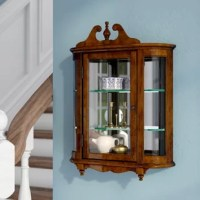 Display your decor in traditional style with this beautiful cabinet, must-have addition to classic ensembles. It is the perfect choice for stowing china in the dining room or showing you're curious in the entryway. The wood frame with glass panels anchor this piece in traditional style, while the scrolling top design and finial accent add a touch of artful appeal. This cabinet features a wall-mounted design that adds essential stability. Try adding it to your entryway, then fill it with family...