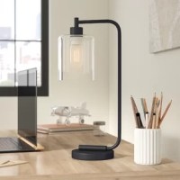 A sophisticated take on an industrial design, this table lamp lends a touch of buttoned-up appeal to your room's aesthetic. Made from iron in a handsome matte black finish, this charming design showcases a tubular metal body, a chunky circle pedestal base, and an exposed finial bulb ensconced in a clean-cut cylindrical clear glass shade. Add this alluring lamp to your nightstand or desk to illuminate your late-night work sessions in a warm glow.