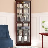 Clean-lined, sleek appeal meets understated style with this essential curio cabinet, the perfect piece for your well-curated and eclectic display space. Featuring a corner-fitting design, this curio cabinet creates display space in any environment, while the warm finished manufactured wood frame adds a dash of earthy appeal to the room. Station this cabinet in a corner of your dining room to arrange cherished family heirlooms and china on its five tempered glass shelves, then turn on the top...