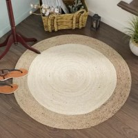 Bring simple style to your floors with this hand-woven 100% jute area rug, crafted in India. This handsome rug's two-tone ivory and natural palette let you lean into both monochromatic or vibrant spaces, while its .5