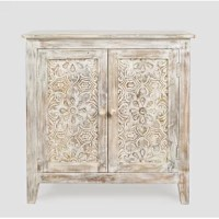 Add a French country accent to your living room, dining room, or kitchen with this 2-door accent cabinet. Crafted from a blend of solid and engineered wood, this piece features intricate carved mango wood designs on its panel doors, and heavy distressing for a rustic look. Its double doors feature handy magnetic latches, and open up to reveal one shelf and space for books, dishes, and other personal items, while its 32'' W surface hosts framed photos or favorite accent lamp.   Hand-curated...