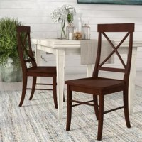 Blending breezy coastal style with approachable traditional design, this Brookwood Solid Wood Side Chair lends your dining room a dash of timeless appeal. Made from solid rubberwood, this dapper design showcases a classic cross-back backrest, a gently contoured seat, and four subtly curved square legs in a calming solid hue. Establish casual, coastal aesthetic in your dining room by rolling out a blue and white striped area rug for a pleasant pop of pattern, then pull six of these stylish...