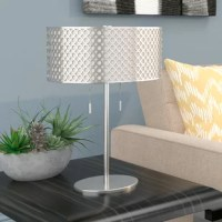 Offering eye-catching allure and illumination for your ensemble, this table lamp is sure to shine no matter where you set it. Try it on an end table beside your sofa to liven up your living room look, or pop it onto your nightstand for a mini master suite makeover. Crafted of metal, it features a simplistic frame finished in metallic for a look of modern elegance. Up top, you'll find two lights highlighted by a matching frosted glass and metal shade with a rounded silhouette and a pierced...