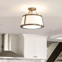 Chipley is an updated traditional design featuring a richly textured off-white fabric shade captured by wide solid metal uprights and trim rings. The domed bottom diffuser is captured inside a heavy trim ring and held by cast decorative knobs for a refined vintage touch.