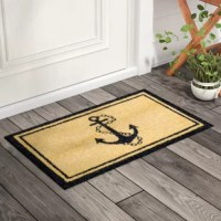 Welcome guests to your home with splash of nautical flair by laying out this fun, anchor-themed doormat. Machine made in India, this charming design is tufted from natural coco fiber in a low-clearance pile to make it easy for doors to open over it. Striking a clean rectangular silhouette, this doormat features a two-stripe border, while a bold anchor graphic sits in the center of the piece. Designed to stand up to foot traffic and add some character to your doorway, a plastic PVC backing helps...