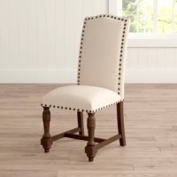Brimming with timeless appeal, this cotton-and-linen upholstered side chair rounds out your favorite seating space in casual charm. Its nailhead trim adds a refined touch to your decor, while its turned legs add traditional flair to any space. Play up this piece's versatility by adding it to a traditional living room seating space alongside a Chesterfield sofa and matching wingback armchairs for a cohesive arrangement, then anchor the space with a pedestal-base coffee table, perfect for...