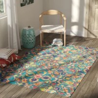 """A bright and vibrant update on vintage Eastern patterns and prints, this hand-tufted area rug showcases an eye-catching oriental floral motif in saturated hues of blue, green, red, and gold. Made in India from 100% wool in a .5"""" loop pile, this sophisticated design adds a perfect touch of softness to the bedroom or the den. Available in a variety of sizes and silhouettes to suit your unique needs, this rug works best when paired with a rug pad."""
