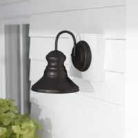 Perfect for the porch, patio, deck, garage, column, or any walled structure, this modern one-light outdoor barn light adds a touch of industrial flair to the exterior of your home. Inspired by utilitarian lights found on naval ships and coastal structures, this light features a raised circle backplate, a tall, curved arm, and an inverted bowl shade. Crafted from aluminum in a weather-resistant finish, this charming design is available in a variety of colors and sizes to suit your style needs.